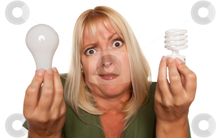 Funny Woman Holding Energy Saving and Regular Light Bulbs stock photo, Funny Faced Woman Holds Energy Saving and Regular Light Bulbs Isolated on a White Background. by Andy Dean