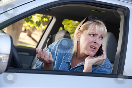 Concerned Woman Using Cell Phone While Driving stock photo, Concerned Blonde Woman Using Cell Phone While Driving. by Andy Dean