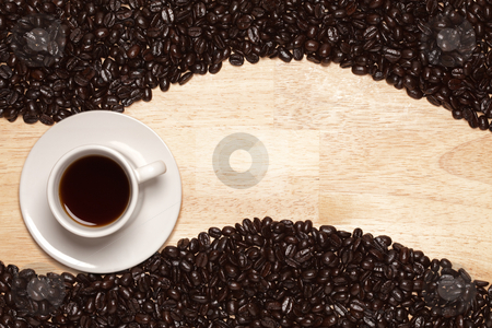 Dark Roasted Coffee Beans and Cup on Wood Background stock photo, Dark Roasted Coffee Beans and Cup with Saucer on a Wood Textured Background. by Andy Dean