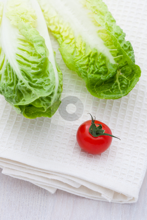 Two lettuce leaves and a cherry tomato stock photo, Two lettuce leaves and a cherry tomato on a napkin by Robert Anthony