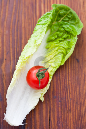 Lettuce leaf and a cherry tomato stock photo, Lettuce leaf and a cherry tomato on a wooden background by Robert Anthony