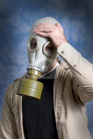 Chemical Headache stock photo, Concept image of a young man suffering from a headache while wearing a gas mask by Richard Nelson
