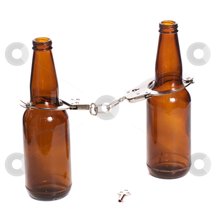 Arrested Drunk stock photo, Concept image of getting arrested while being drunk, shown with two beer bottles with handcuffs on by Richard Nelson