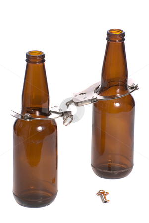Beer Bottles With Handcuffs stock photo, Concept image of getting arrested while being drunk, shown with two beer bottles with handcuffs on by Richard Nelson