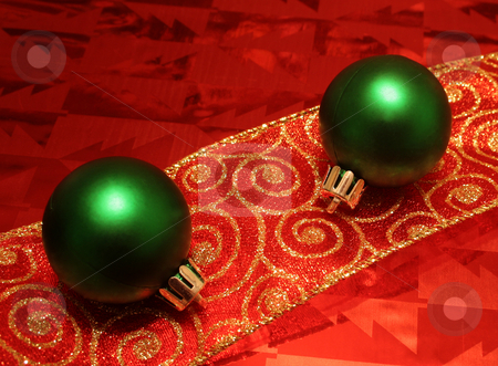 Two Green Balls on a Ribbon stock photo, Two green christmas ball decorations, resting on a ribbon and wrapping paper. by Chris Hill