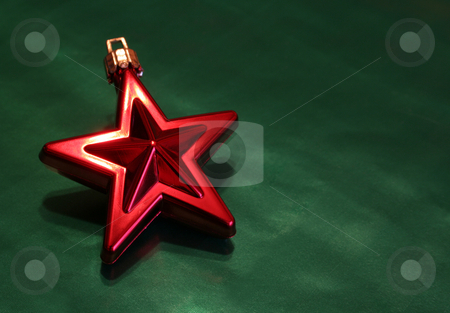 Shiny Red Christmas Star stock photo, A shiny red Christmas star ornament sitting on green wrapping paper. by Chris Hill
