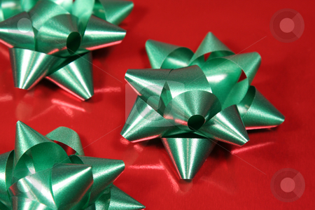 Green Xmas gift bows stock photo, Green Xmas gift bows on red glossy paper. by Chris Hill