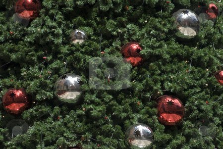 Faux Christmas Tree stock photo, An artificial Christams tree background with red and silver metallic baubles by Stephen Gibson