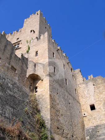 Ancient castle stock photo, Walls of the ancient castle on the background of blue sky by Olga Lipatova