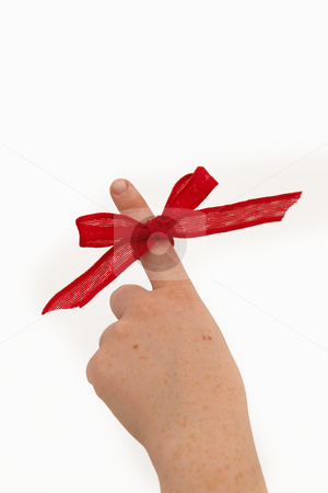 Pointing a ribbon on a finger stock photo, Womans hand with red ribbon pointing upwards by Phillip Dyhr Hobbs