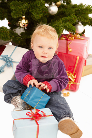 Christmas - Cute child opening gifts  stock photo, Christmas - Cute child opening gifts on x-mas day by Phillip Dyhr Hobbs
