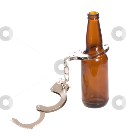 Illegal stock photo, Concept image of drinking illegally featuring a beer bottle and a pair of handcuffs, isolated against a white background by Richard Nelson