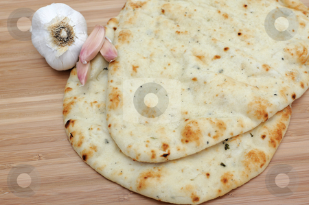 Garlic Naan stock photo, Garlic flavored East Indian Naan flat bread with fresh garlic cloves on a wooden cutting board by Lynn Bendickson
