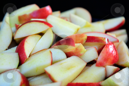 Apple Slices stock photo, Red Apples sliced up into many small pieces with a dark background by Lynn Bendickson
