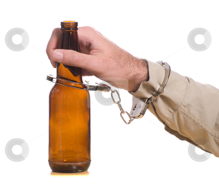 Drinking and Driving stock photo, A mans hand is handcuffed to a bottle of beer, isolated against a white background by Richard Nelson