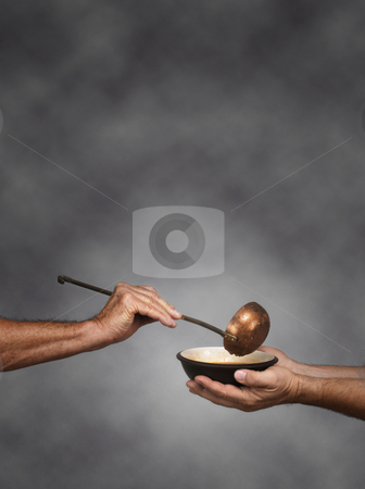 Feed the world vertical stock photo, Vertical composition of a man holding a bowl in both hands, receiving a serving of soup from another man holding a soup ladle by James Steidl