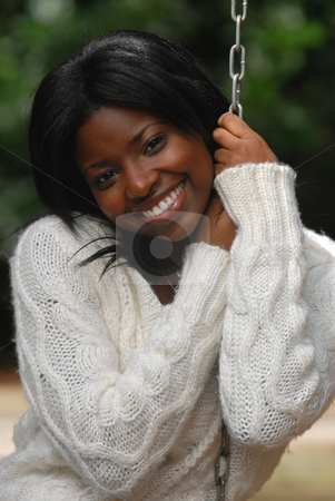 African-American woman smiles stock photo, African-American woman smiles while sitting in a swing by Hasan Shaheed