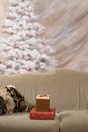 Christmas Gifts stock photo, Two Christmas gifts lying on a sofa with a hand painted Christmas tree in the background by Richard Nelson