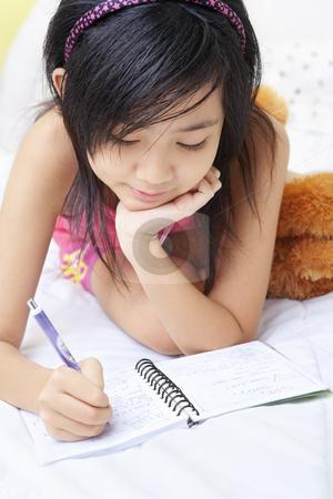 Little girl writing her diary stock photo, A little girl writing her diary in her bedroom by Rudyanto Wijaya