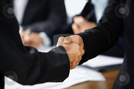 Handshake between two businesswoman stock photo, Handshake between two businesswoman with other business people on background. Different skin tones by Rudyanto Wijaya