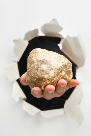 Hand breakthrough wall holding big lump of golden nugget stock photo, Hand breakthrough wall holding lump of golden nugget means breaktrhough in finance or similar things - one of the breakthrough series by Rudyanto Wijaya