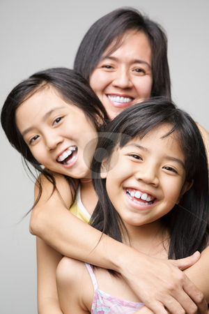 Mother and daughters stock photo, Mother hugging her daughters and posing to camera by Rudyanto Wijaya