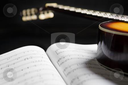Classic guitar and music chords stock photo, Classic guitar on top of music chords against dark by Rudyanto Wijaya