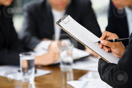 Hand writing with other business people in background stock photo, Businesswoman's hand writing with other business people in background by Rudyanto Wijaya