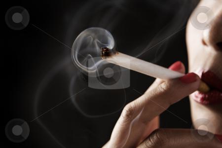 Woman smoking with smoke shaped like skeleton stock photo, Woman smoking on dark area with smoke shaped like skeleton ( I added the jaw detail) on dark area by Rudyanto Wijaya