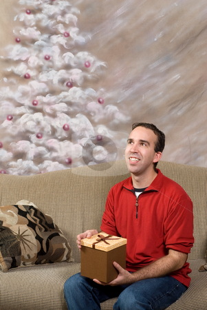 Christmas Morning stock photo, A man dressed in a red sweater and blue jeans is holding a Christmas present by Richard Nelson