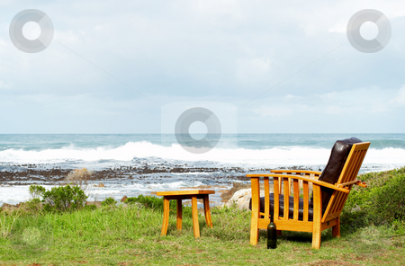 Wooden chair standing outside stock photo, Wooden chair standing outside by the ocean on a sunny summer day with blue skies and waves in the background by Elena Weber (nee Talberg)