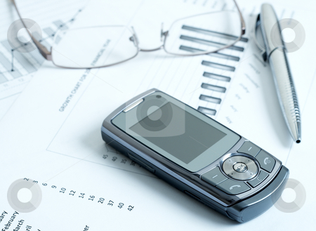 Cellphone with pen and glasses stock photo, Close-up of cellphone with modern silver pen and reading glasses on top of potential growth charts and graphs. Blue tone image by Elena Weber (nee Talberg)