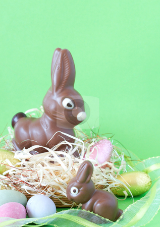Two chocolate Easter bunnies stock photo, Two chocolate Easter bunnies with colorful chocolate eggs in straw by Elena Weber (nee Talberg)