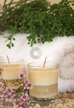 Relaxing spa scene stock photo, Relaxing spa scene with a white rolled up towel, pink flowers and green filler, beautiful handmade candles and bath salts by Elena Weber (nee Talberg)