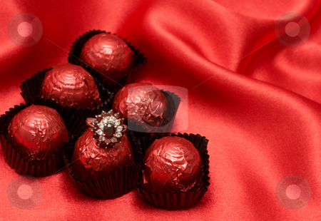 Valentines chocolate candy with a ring stock photo, Valentines chocolate truffles with an expensive engagement ring shot on red silk background by Elena Weber (nee Talberg)