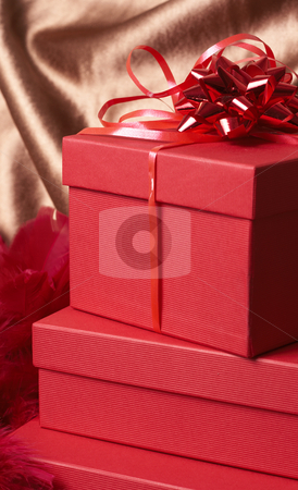 Stack of red gift boxes  stock photo, Stack of red gift boxes with bows and feathers on golden silk background by Elena Weber (nee Talberg)