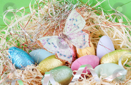 Colorful wrapped chocolate Easter eggs stock photo, Assortment of chocolate Easter eggs wrapped in colorful paper with butterfly on top by Elena Weber (nee Talberg)