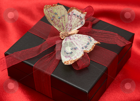 Valentines gift on red silk stock photo, Valentines gift box with red ribbon and colorful butterfly on red silk by Elena Weber (nee Talberg)