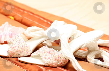Bridal shoes with beads stock photo, White bridal shoes adorned with pink, white and silver beads lying on brown bed cover by Elena Weber (nee Talberg)