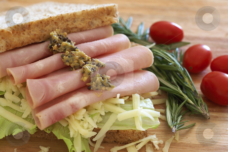 Tasty open sandwich on wholewheat bread stock photo, Tasty open sandwich with green lettuce, grated cheese, smoked ham and wholegrain mustard on wholewheat bread with rosemary and tomatoes on chopping board by Elena Weber (nee Talberg)