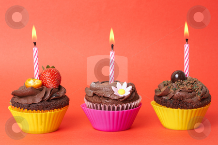 Miniature chocolate cupcakes with candles stock photo, Three miniature chocolate cupcakes with icing, decorations and birthday candles on red background by Elena Weber (nee Talberg)
