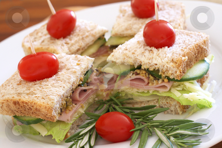 Tasty sandwiches on wholewheat bread stock photo, Tasty club sandwiches with green lettuce, grated cheese, smoked ham and wholegrain mustard on wholewheat bread with rosemary and tomatoes by Elena Weber (nee Talberg)