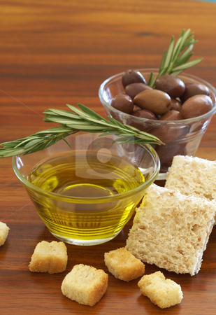 Two jars of black olives and olive oil stock photo, Two jars of black olives with stick of rosemary, olive oil, wholewheat bread and croutons on wooden table background by Elena Weber (nee Talberg)