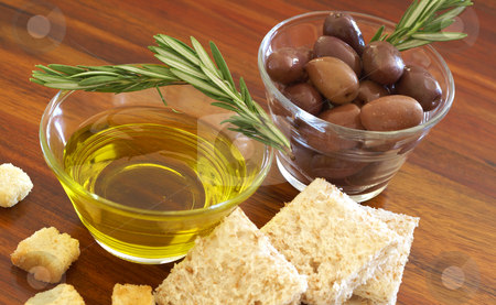 Two jars of black olives, oil and croutons stock photo, Two jars of black olives with stick of rosemary, olive oil, slices of bread and croutons on wooden table background by Elena Weber (nee Talberg)
