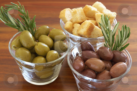 Two jars of green and black olives and croutons stock photo, Two jars of green and black olives with stick of rosemary and croutons on wooden table background by Elena Weber (nee Talberg)
