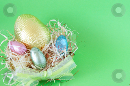 Easter chocolate eggs stock photo, Assortment of chocolate Easter eggs wrapped in colorful paper in straw by Elena Weber (nee Talberg)