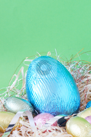 Colorful wrapped chocolate Easter eggs stock photo, Assortment of chocolate Easter eggs wrapped in colorful paper in straw by Elena Weber (nee Talberg)