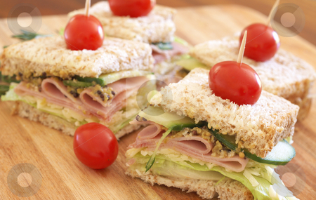 Tasty club sandwich on wholewheat bread stock photo, Tasty club sandwich with green lettuce, grated cheese, smoked ham, cucumber and wholegrain mustard on wholewheat bread with tomatoes on chopping board by Elena Weber (nee Talberg)