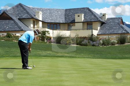 Golfer on the putting green stock photo, Golfer on the putting green next to a luxurious house by Elena Weber (nee Talberg)