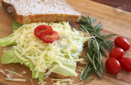 Tasty open sandwich on wholewheat bread stock photo, Tasty open sandwich with green lettuce and grated cheese on wholewheat bread with rosemary and tomatoes on chopping board by Elena Weber (nee Talberg)